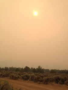 The sun shines orange as it barely is seen through a thick cloud of smoke from the King Fire in California