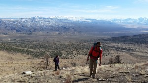Anna Ortega (right) and Maggie Gray (left) hike toward a fire rehabilitation site where mountain mahogany seedlings will be planted.