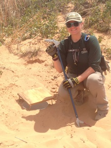 Here I am showing off one of the lizard pitfall traps. It is a 5-gallon bucket buried into the sand, with the opening canopied by a small piece of plywood that keeps the critters shaded and predators out of the traps. Photo taken by N. Montoya.